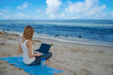 Fototapety Yang woman with laptop by the ocean