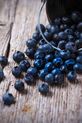 Some Blueberries in a small Bucket on wooden background