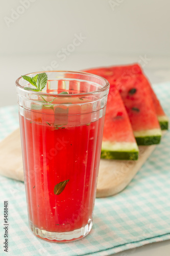 Glass of watermelon smoothie isolated on white.