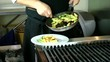 Chef serving rigatoni in the kitchen