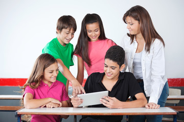 Schoolboy Pointing At Tablet With Classmates In Classroom