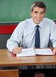 Male Teacher Sitting With Pen And Binder At Desk