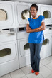 Confident Female Helper Standing By Dryers