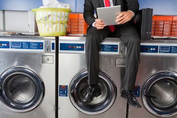 Businessman Using Digital Tablet While Sitting On Washing Machin