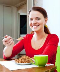Happy girl in red eats buckwheat
