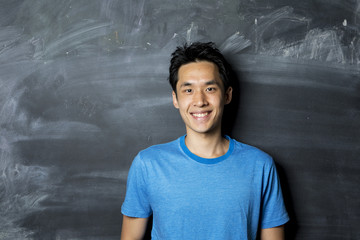 Happy Asian man standing next to a blackboard.