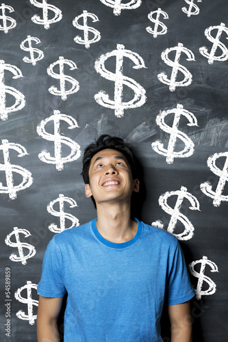 Chinese man standing in front many dollar sign written on a chal