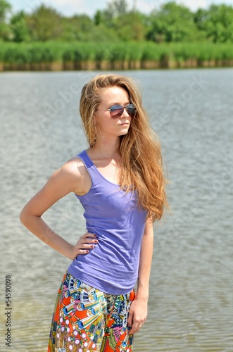 young beautiful girl on the bank of the river