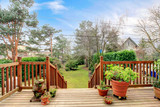 Wood deck with railings and spring back yard garden