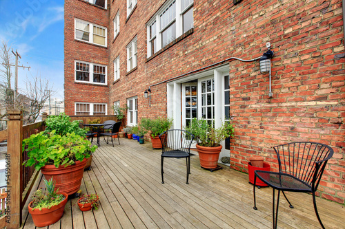 Brick apartment building large outdoor terrace.