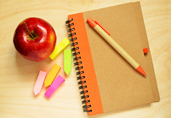 Notebook, pen,  stickers and apple