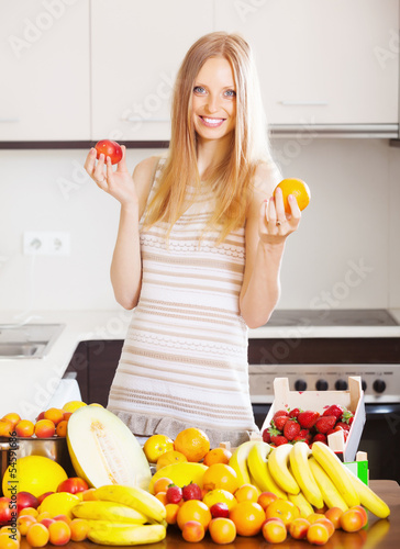 blonde long-haired woman with heap of ripe fruits