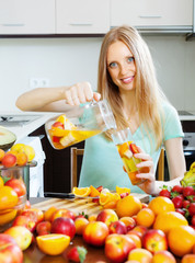 cheerful woman pouring beverages with fruits