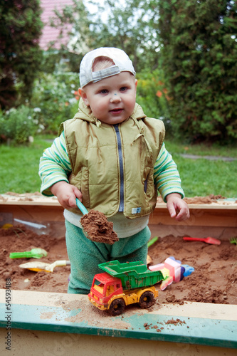 working boy playing in a sandbox