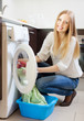 Happy blonde woman loading clothes into the washing machine