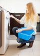 Long-haired woman with washing machine