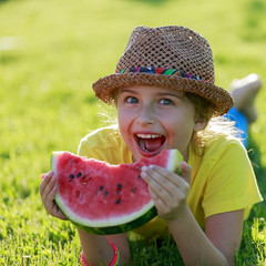Summer joy - girl eating fresh watermelon in the garden