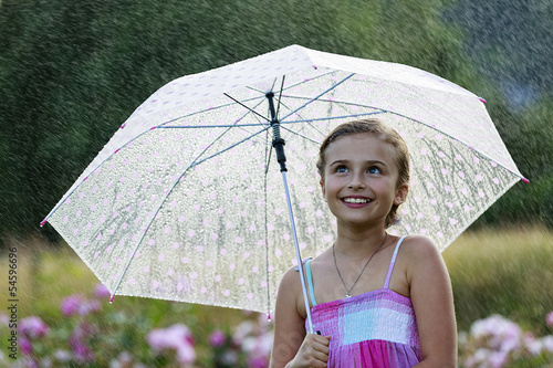Summer rain - happy girl with umbrella in the rain