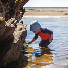 Young Child at Beach Plays in Rock Pool.
