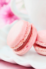 Pink French macaroons with a cup of coffee