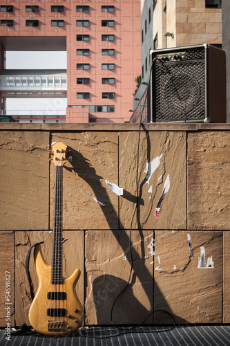 Bass guitar and amplifier against a wall