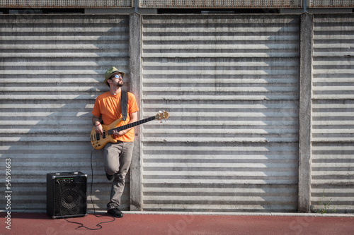 Young musician playing bass guitar
