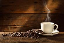 "Постер, картина, фотообои ""Coffee cup and coffee beans on old wooden background"""