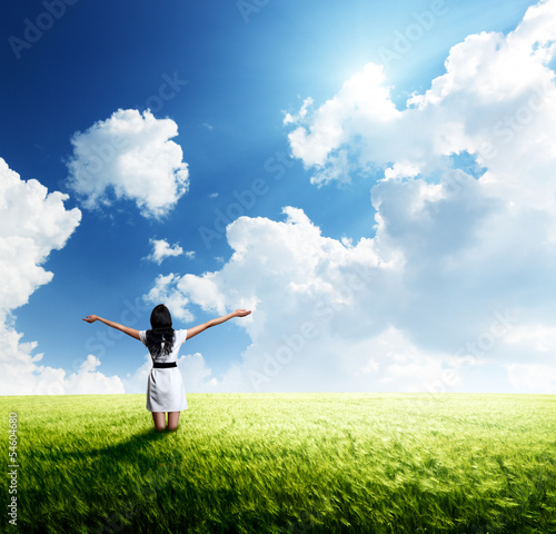 happy young woman in white dress standing at field