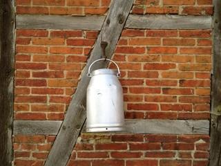 Milchkanne hängt an Wand