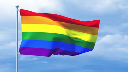 LGBT flag waving over a cloudy blue sky