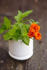 Mint and marigold flowers in mortar