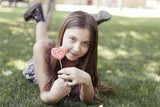 Girl with colouring lollipopon grass