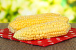 Fresh corn on bamboo mat, on wooden background