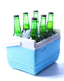 Bottles of beer with ice cubes in mini refrigerator, isolated