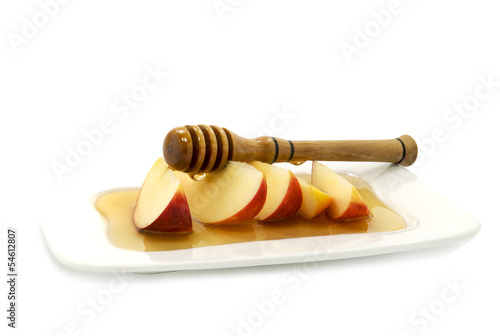 Honey dripping on red apple slices isolated on white