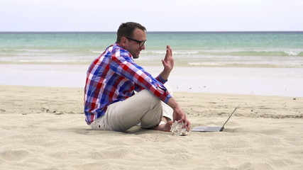 Man using chatting with laptop on the beach, slow motion shot at