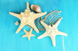 White starfishes on blue wooden table close-up