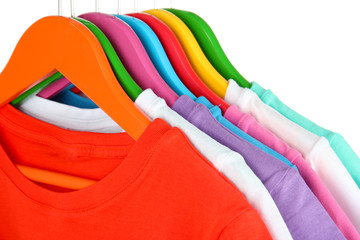 Different shirts on colorful hangers on white background
