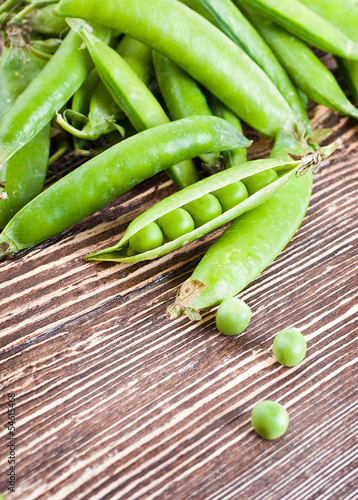 Ripe green peas on a wooden board