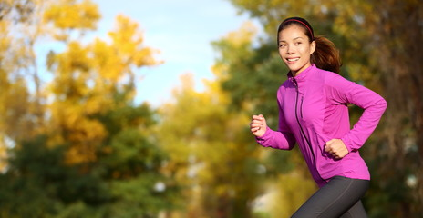 Female runner running in fall forest outside