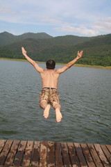 a asia man jump to lake water with mountain view background