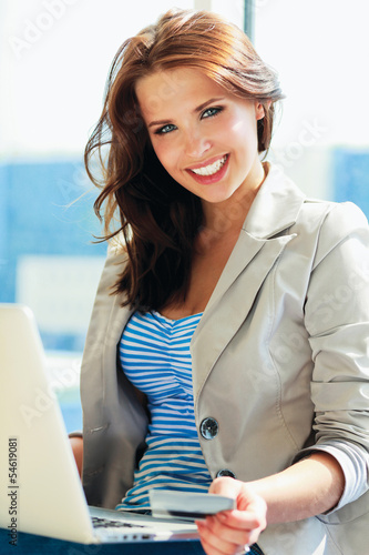 Young  woman sitting with laptop and credit card