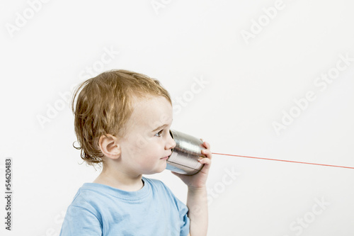 young child with tin can phone
