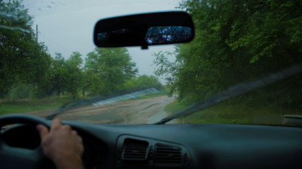 Man driving along the road under the rain