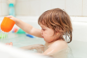 kid bathes with toys in bath
