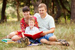 Happy father, mother and son reading book