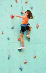 smiling child climbing up the wall