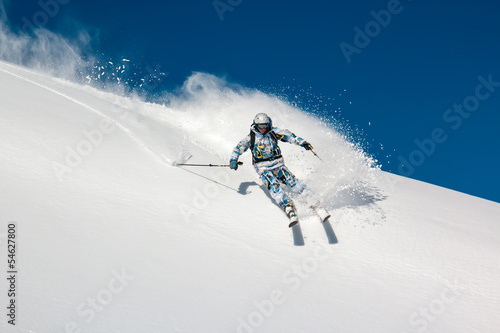 Skier on a steep mountain slope. In turn raises the snow dust.