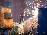 Arc welder worker in protective mask welding metal construction