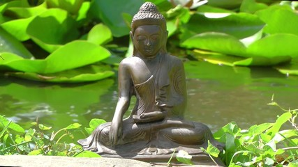 Buddha seated by a pool